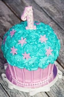 Tarta de primer cumpleaños con una unidad sobre un fondo morado con bolas y guirnalda de papel.