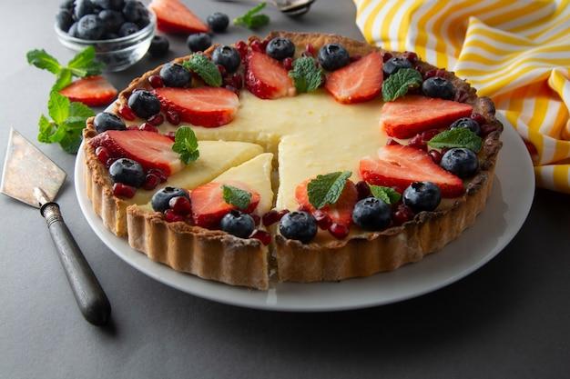 Tarta de queso con bayas frescas y menta para el postre. fondo gris