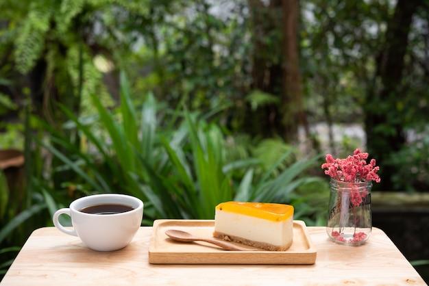 Tarta de queso y café caliente en bandeja de madera y mesa