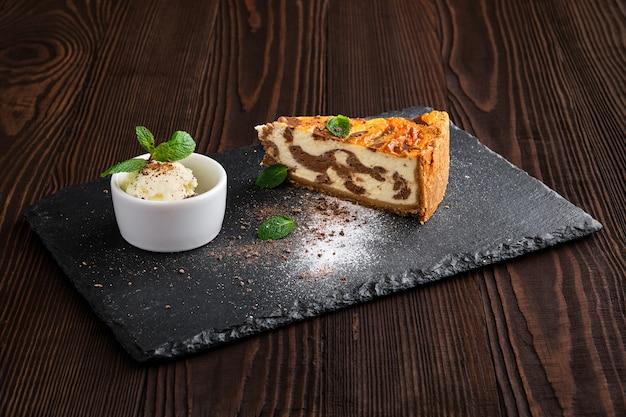 Tarta de queso en capas con helado servido en plato de pizarra en la mesa de madera oscura