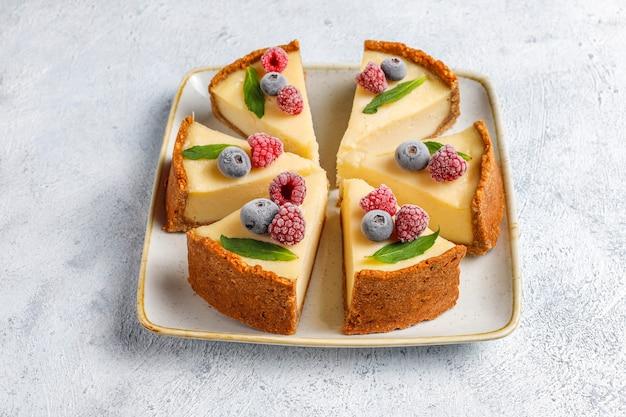 Tarta de queso casera de nueva york con bayas congeladas y menta, postre orgánico saludable, vista superior