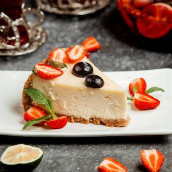 Tarta de queso clásica con rodajas de fresa y cereza
