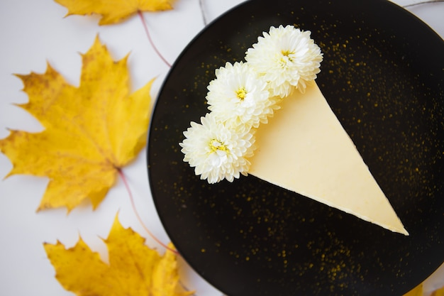 Tarta de queso cremoso, hojas y flores amarillas de otoño, primer plano