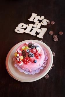Tarta de queso dulce con bayas frescas y crema de yogur y letrero de madera its a girl. fiesta de baby shower dulces.