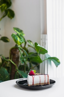 Tarta de queso dulce con bayas frescas en un plato de cerámica negro sobre la mesa blanca