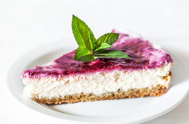 Tarta de queso de frambuesa con hojas de menta sobre fondo blanco, concepto, confitería