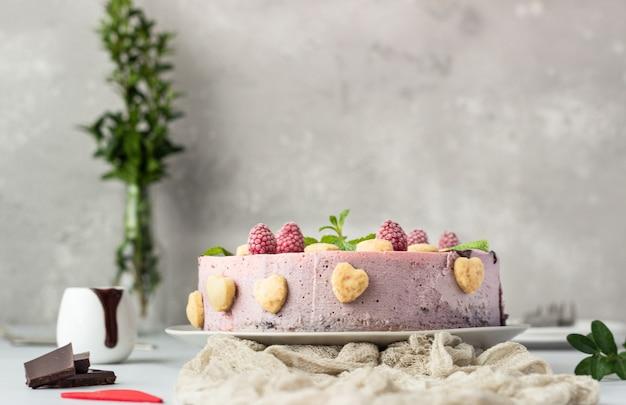 Tarta de queso de frambuesa sin hornear con glaseado de chocolate, frambuesas, galletas y menta
