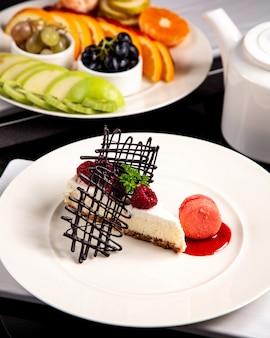 Tarta de queso con frambuesa y plato de fruta
