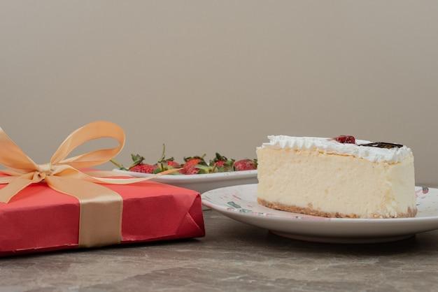 Tarta de queso, fresas y una caja de regalo sobre mesa de mármol.