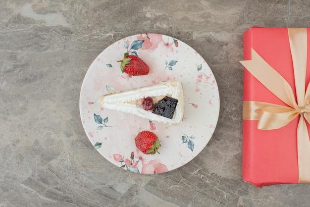 Tarta de queso con fresas y un regalo en mesa de mármol.