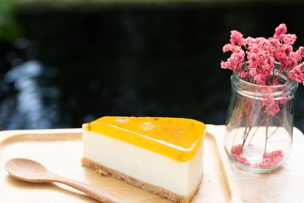 Tarta de queso de fruta de la pasión servida en madera tay y mesa de madera con florero seco