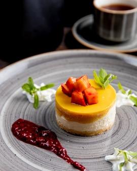 Tarta de queso con frutas en la parte superior servida con salsa de bayas