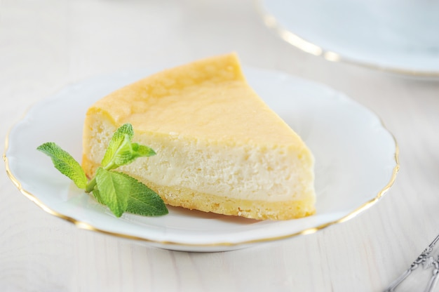 Tarta de queso y una hoja de menta en el plato con un borde dorado
