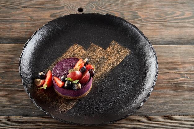 Tarta de queso morado con frutos rojos en un plato
