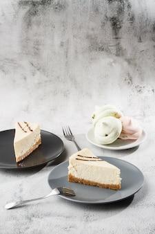 Tarta de queso nueva york o tarta de queso clásico con una taza de café en la mesa blanca. vista de cerca desayuno sabroso pedazo de pastel en plato negro, taza blanca sobre fondo de mármol blanco. foto vertical.