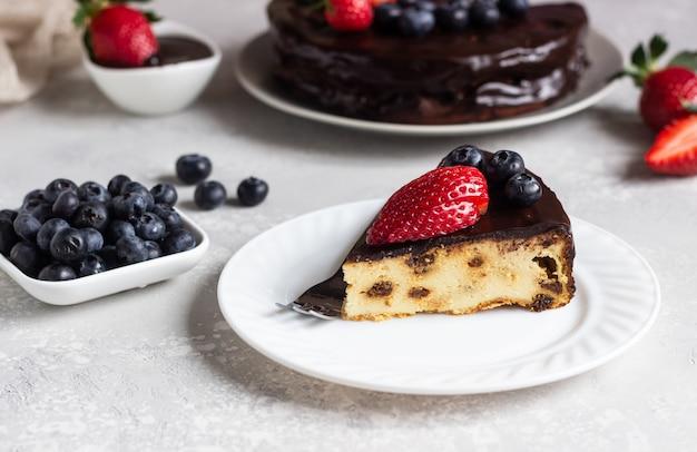 Tarta de queso con pasas decorado con glaseado de chocolate y fresas y arándanos.