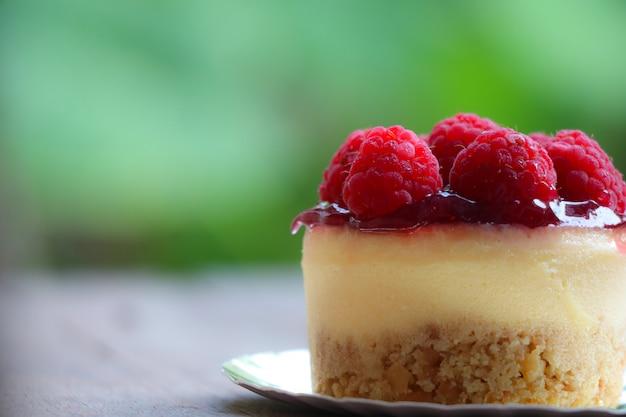 Tarta de queso rasberry dulce bake topping con fruta sobre fondo de madera