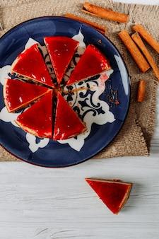 Tarta de queso en rodajas con palitos de canela en un plato y un saco sobre fondo blanco, endecha plana.
