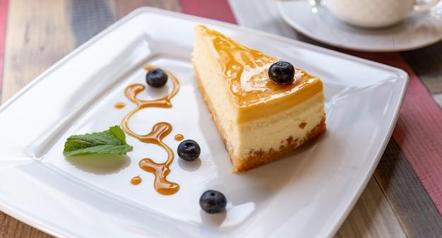 Tarta de queso con salsa de arándanos en un plato blanco y una taza de café en la mesa de madera