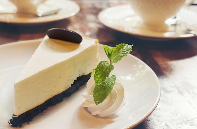 Tarta de queso con taza de café caliente en la cafetería