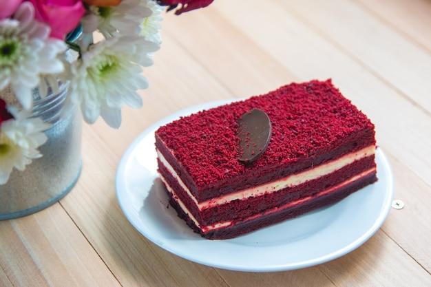 Tarta de queso de terciopelo rojo en plato y ramo rosas
