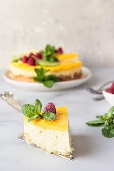 Tarta de queso de vainilla y limón con cuajada de limón decorada con limón y lima, frambuesa y menta