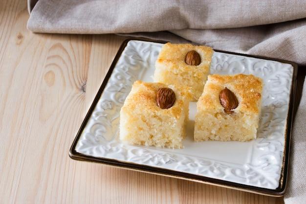 Tarta de sémola árabe tradicional basbousa (namoora) con almendras y almíbar