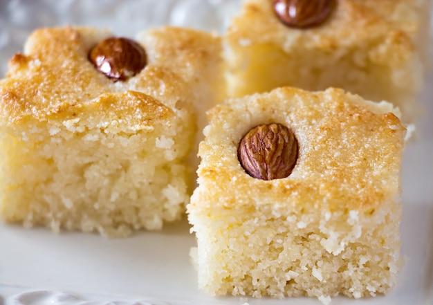 Tarta de sémola árabe tradicional basbousa (namoora) de tres piezas con almendras y almíbar. copia espacio