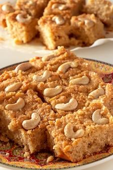 Tarta de sémola árabe tradicional basbousa o namoora con anacardos y jarabe. enfoque selectivo