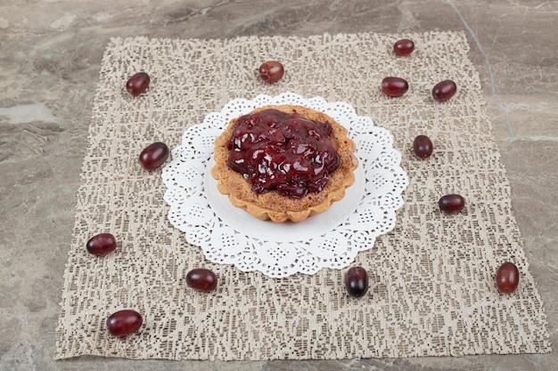 Tarta de tarta con frutas sobre arpillera y uvas.