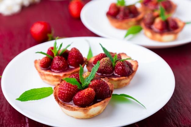 Tartaleta de fresa en platos blancos sobre superficie roja,