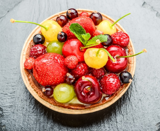 Tartaletas de bayas con arándanos, frambuesas, kiwi, fresas, hojuelas de almendras en azúcar glas.