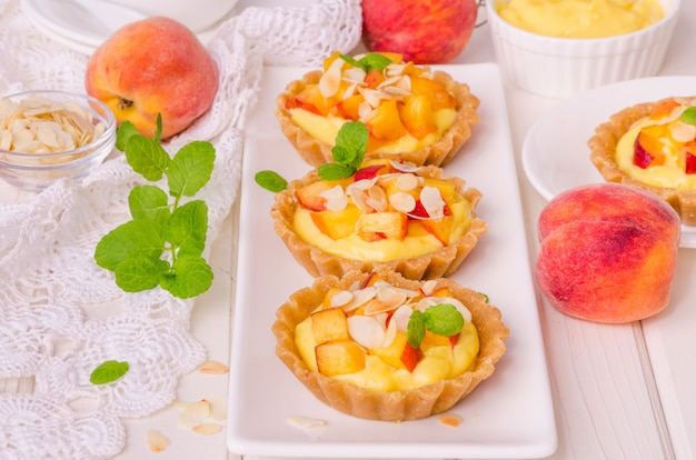 Tartaletas con crema pastelera, duraznos frescos y almendras sobre fondo blanco de madera