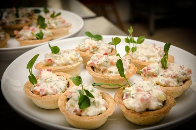 Tartaletas con ensalada de queso crema. vista cercana mesa de buffet de catering
