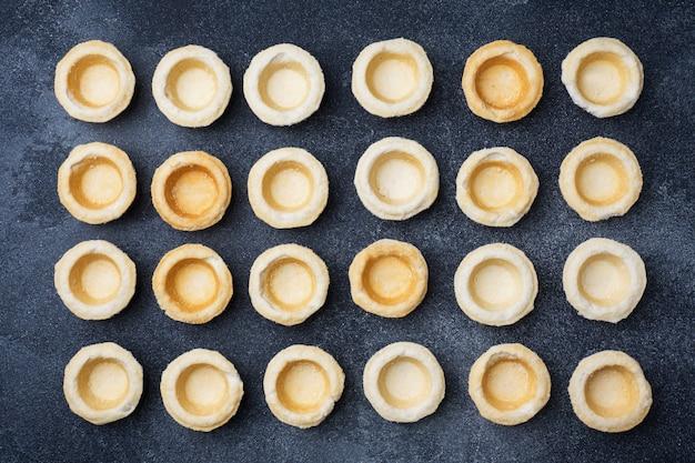 Tartaletas vacías de mantequilla colocadas en una fila. abstracción sobre una superficie oscura.