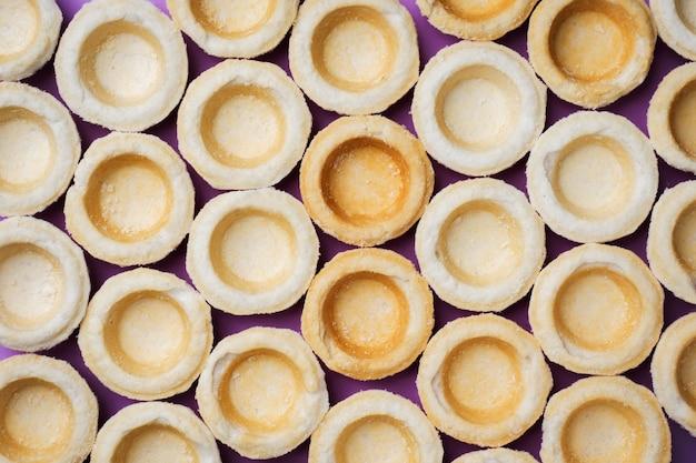 Tartaletas vacías de mantequilla colocadas en una fila. concepto de abstracción en el color de la superficie.