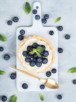 Tartaletas de vainilla con hojas de menta de bayas de arándanos y cubiertos de cuchara de oro sobre fondo claro.