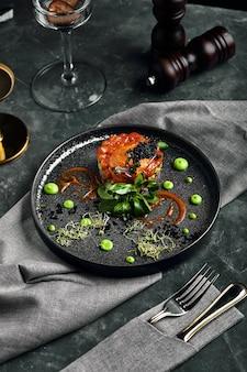 Tartar fresco con salmón, aguacate, caviar rojo en un plato, hermosa porción, hermosa porción, cocina tradicional italiana, fondo gris, espacio de copia