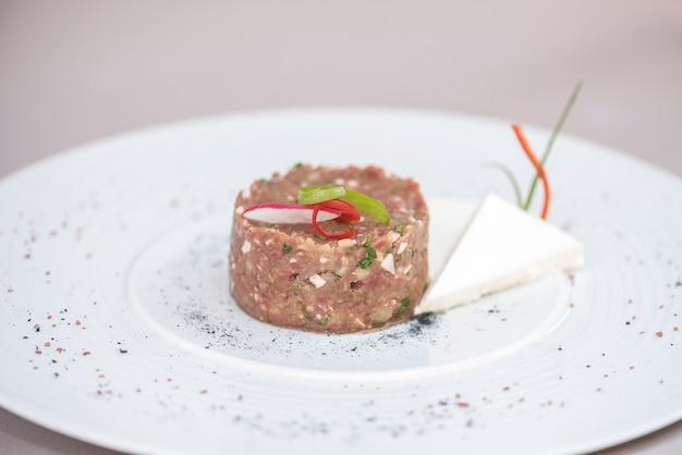 Tartar de ternera clásico, servido con lonchas de queso y decorado con hierbas