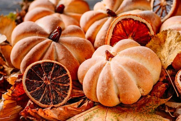 Tartas caseras en forma de calabaza con hojas de otoño de cerca. concepto de dulces de halloween