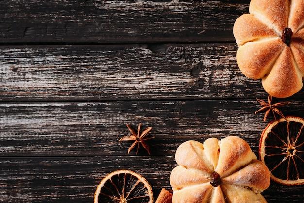 Tartas caseras en forma de calabaza y naranjas secas en madera oscura, vista superior con espacio de copia