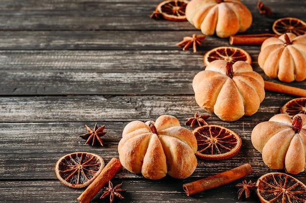 Tartas caseras en forma de calabaza y naranjas secas en una vista superior de fondo de madera oscura con espacio de copia