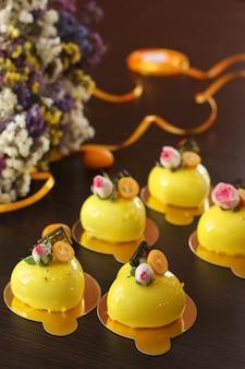 Tartas caseras de mousse brillante corazones con revestimiento de espejo amarillo sobre un fondo oscuro