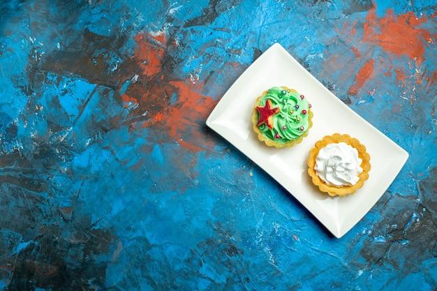Tartas de crema de vista superior en un plato rectangular blanco en el espacio libre de la superficie azul rojo