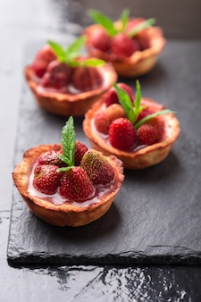 Tartas de fresas caseras en plato de pizarra, negro