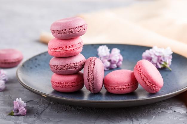 Tartas de macarrón o macarrón morado y rosa en placa de cerámica azul sobre fondo de hormigón gris