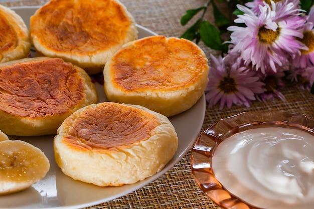 Tartas de queso en un plato sobre un fondo marrón. plato de requesón para el desayuno.