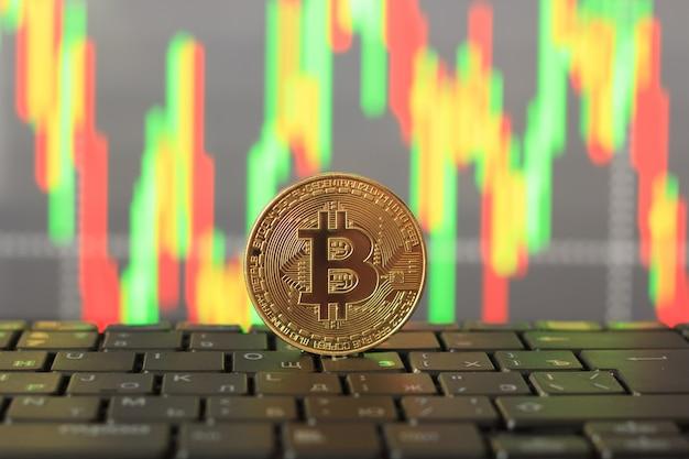 Tasa de bitcoin en la carta y moneda de oro, primer plano