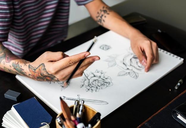 Tatuado a mano dibujando obras de arte