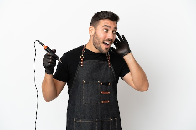 Tatuador hombre aislado sobre fondo blanco escuchando algo poniendo la mano en la oreja